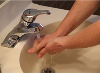 A person washing their hands in the sink.