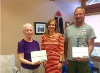 Shannon LaHay, AMGH Foundation Coordinator (c) presents winners Jean Imanse (l) and Bob Orr (r) with their new iPads.